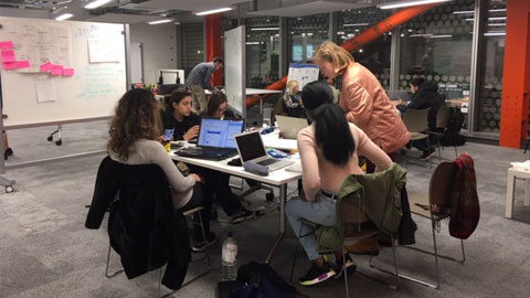Image of group of students working together on laptops as part of the Creative Design Hack.
