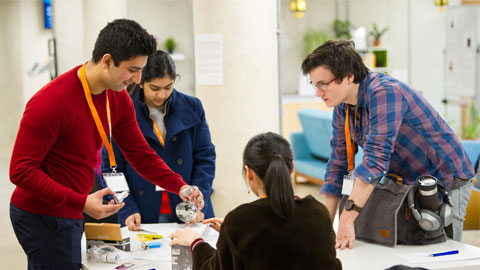 Image of students working collaboratively at a GDI Hub run hackathon.