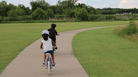 Image of two children riding bicycles.